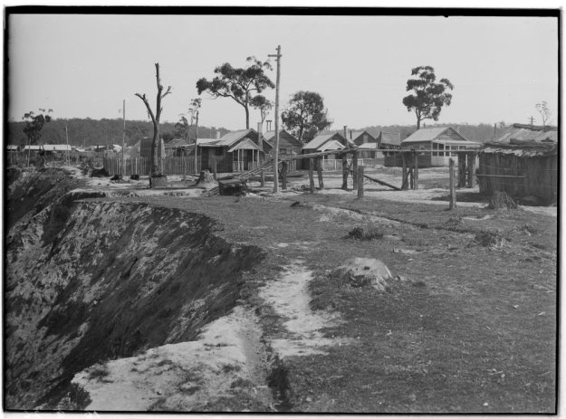 The Brown Coal Mine built on the edge of the Brown Coal Mine. Little shacks, some gum trees.  For original file you can see it - http://search.slv.vic.gov.au/primo_library/libweb/action/dlDisplay.do?vid=MAIN&docId=SLV_VOYAGER2027542&fn=permalink